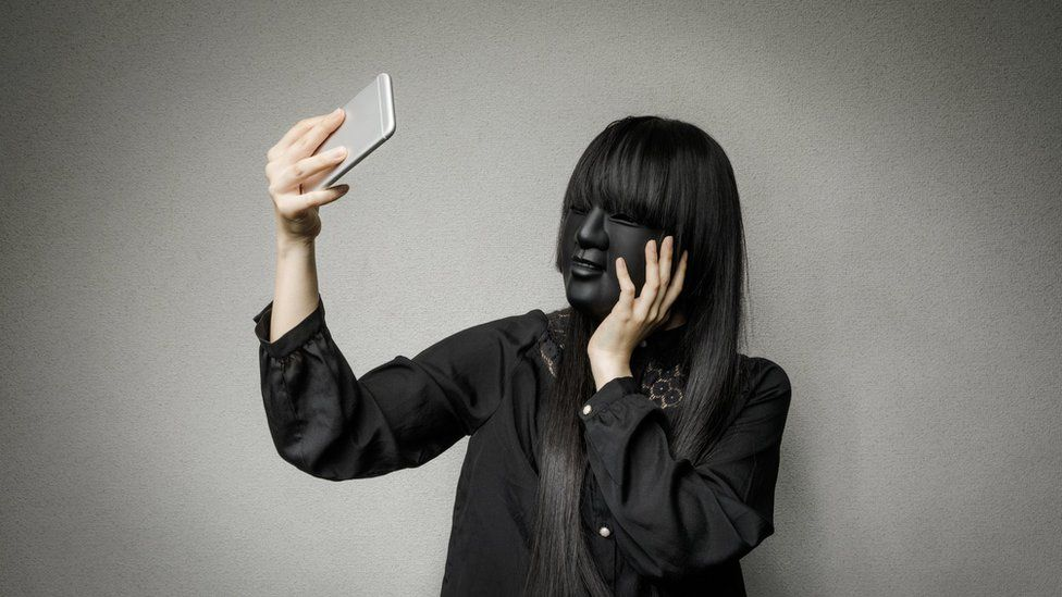 social media screening pros and cons: hiding behind a mask whilst taking a selfie